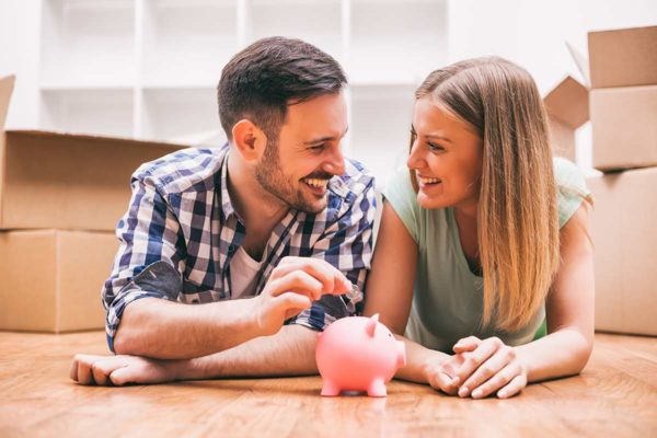 couple saving money in a piggy bank to buy a home