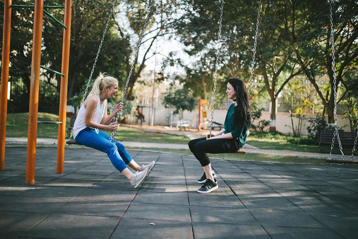friends sitting on swings talking together