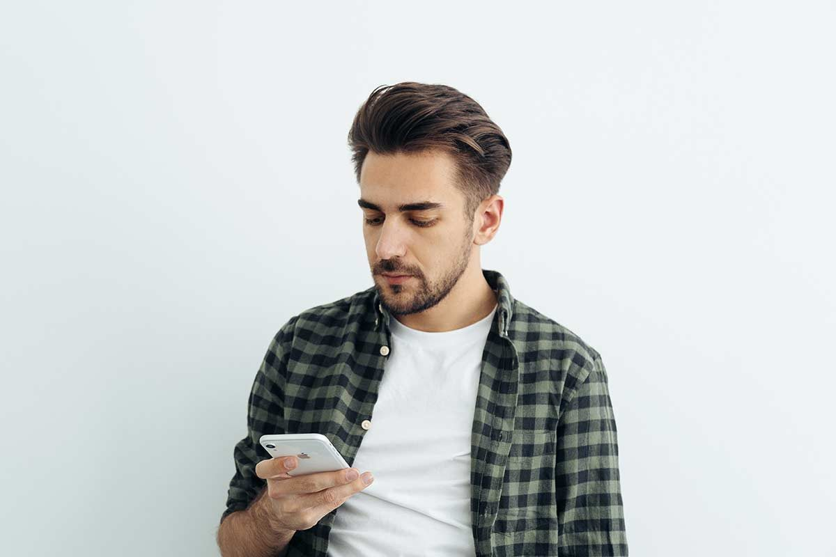 man looking at his white iPhone