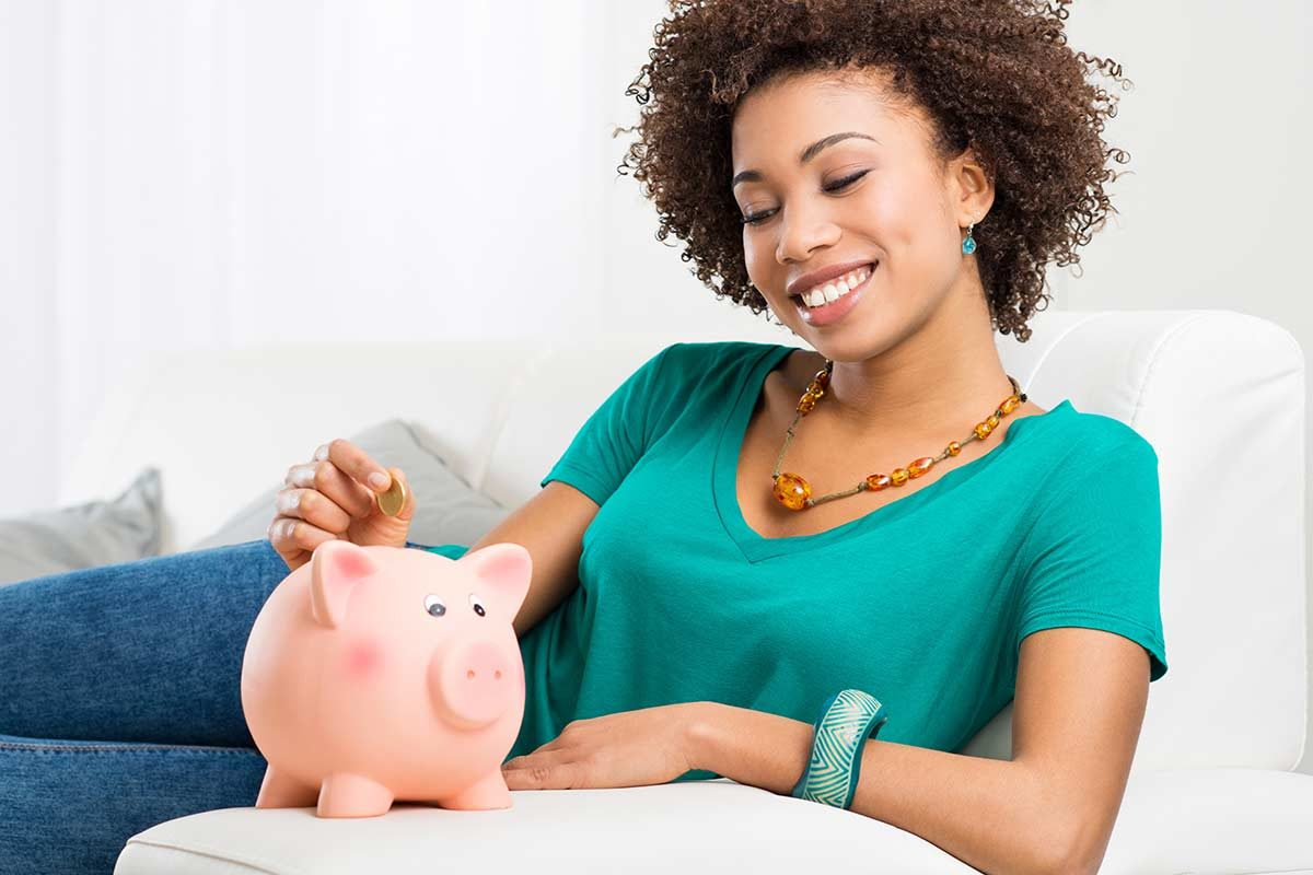 woman saving money into a piggy bank to look after her finances