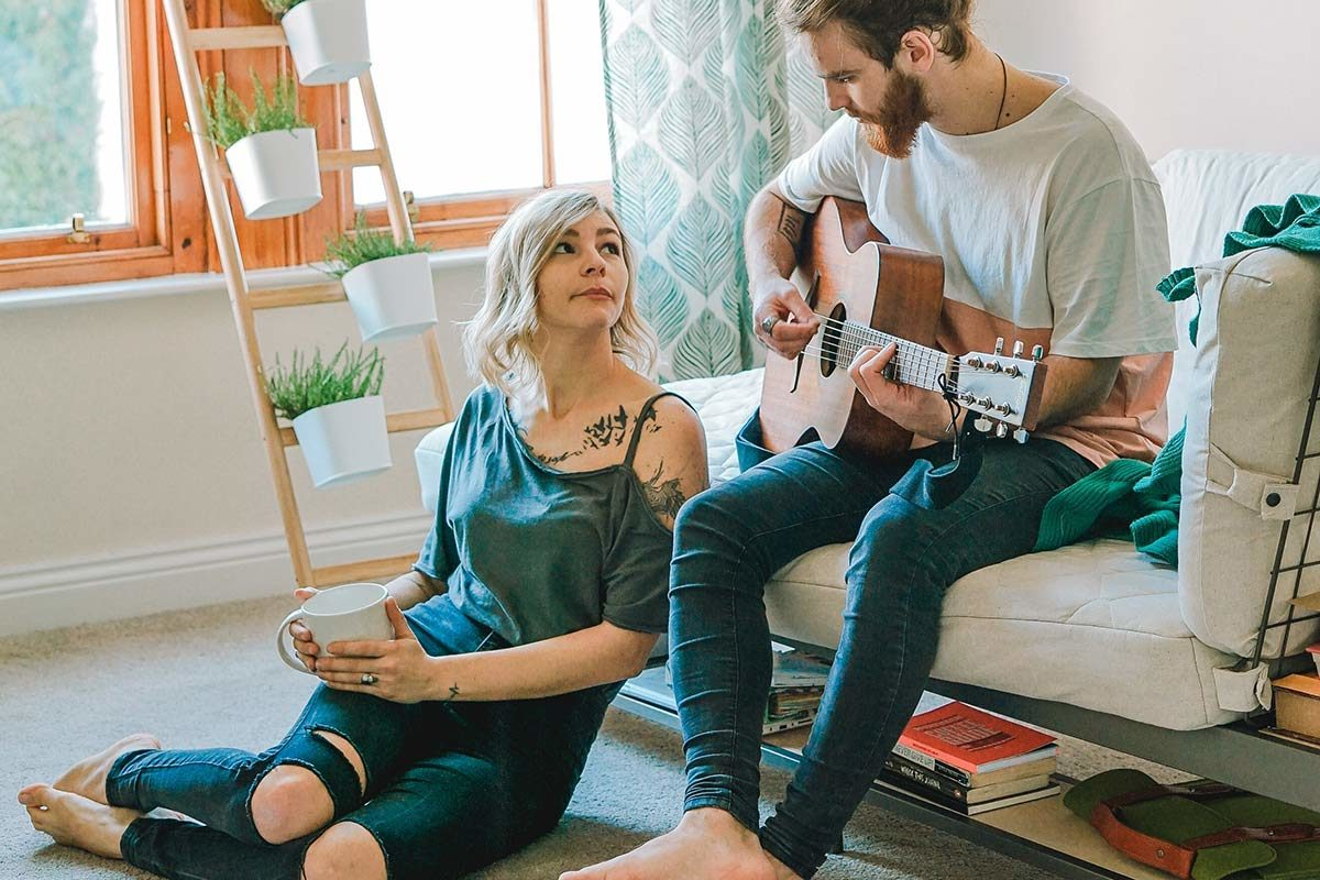 young couple at home - a man playing the guitar while a woman sits on the floor